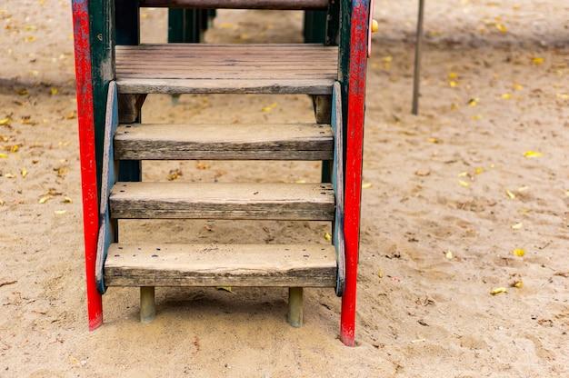 Деревянная лестница на детской площадке на песке в парке