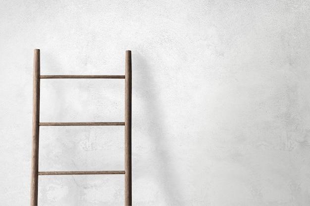 コンクリートの壁にもたれて木製のはしご