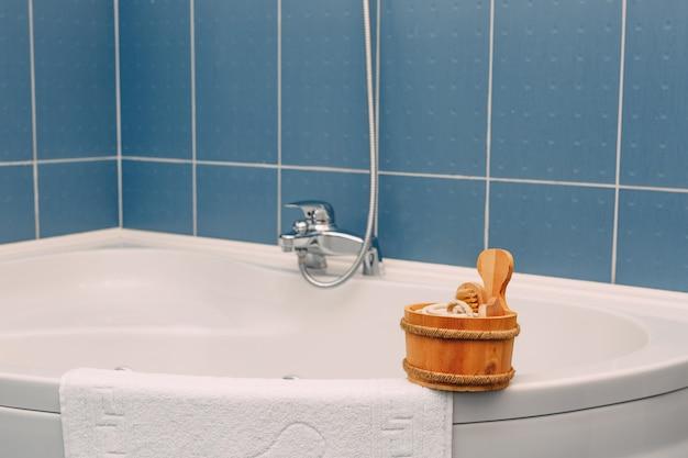 近くの角浴槽の縁にブラシ手ぬぐいと他のシャワーアクセサリーが付いている木製お玉
