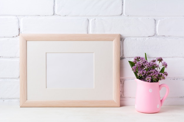 Wooden landscape frame  with purple flowers in pink rustic pitcher