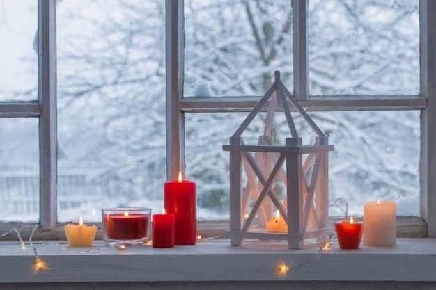冬の風景の窓辺に木製ランタン