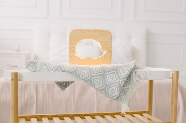 Деревянные лапки и детали декора в домашнем интерьере. стильный деревянный светильник ручной работы с вырезанным изображением ёжика на журнальном столике.