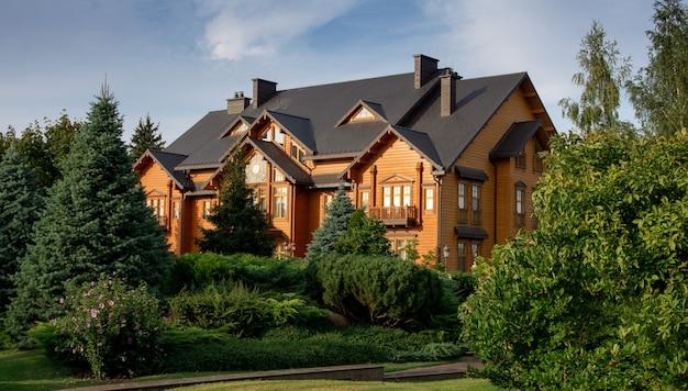 Большой деревянный красивый дом в окружении зеленых деревьев