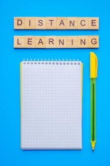 Деревянные кубики письма с фразой дистанционного обучения, блокнот и ручка на синем