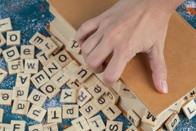 Dadi di lettere in legno sulle pagine di un libro.