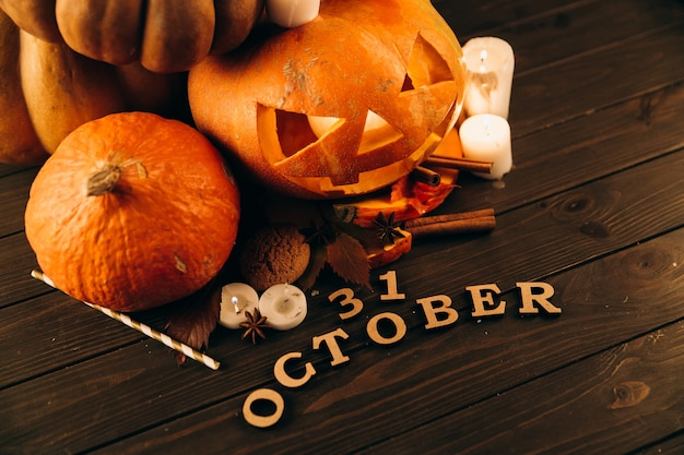 Wooden lettering '31 october' lie before large scarry hallooween pumpkins, candles