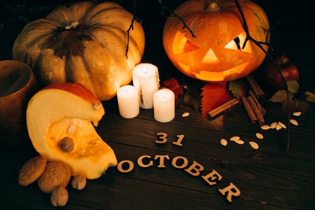 Wooden lettering '31 october' lie before large scarry hallooween pumpkins