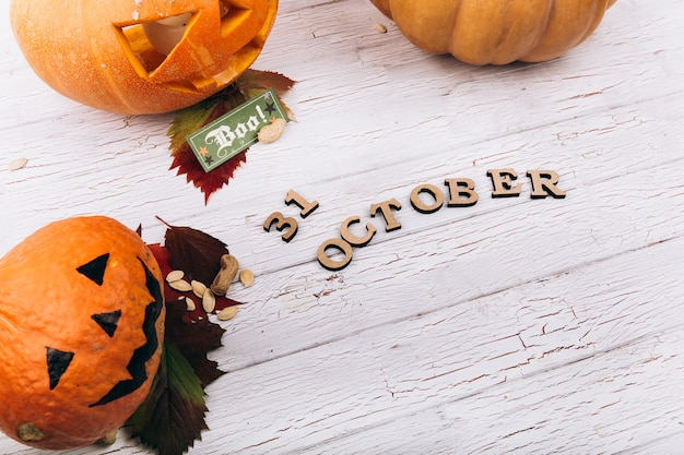 Wooden lettering '31 october' lies before large scarry hallooween pumpkins on white table