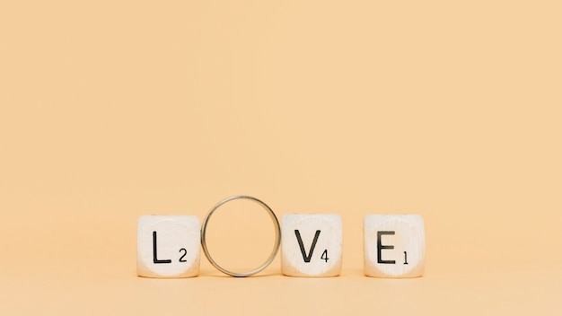 Wooden letters and engagement ring spelling love on beige backdrop