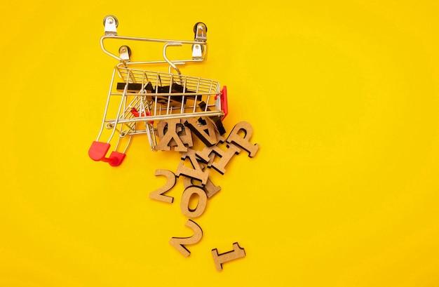 Деревянные буквы упали из продуктовой тележки на желтом фоне.