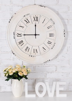 Wooden letters forming word love, flowers in vase and vintage clock over white brick wall background