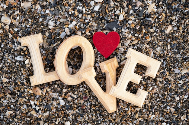 Wooden letters forming the word love with a red heart beach sand. concept of san valentine