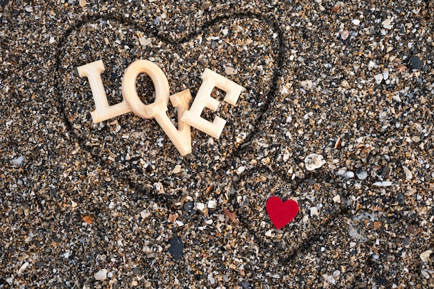 Wooden letters forming the word love with a red heart on beach sand, inside a heart made with the fingers. concept of san valentine