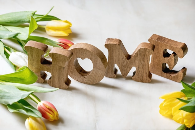 Wooden letters home on a table with tulip flowers