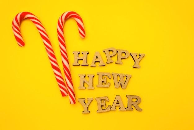 Деревянные буквы в новогодней шапке на желтом фоне с красными конфетами.