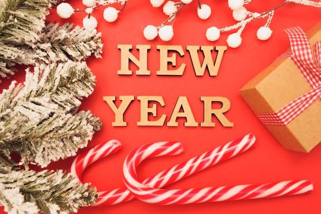 Деревянные буквы в новогодней шапке на красном фоне с зелеными еловыми ветками, конфетами, подарочными коробками и снегом.