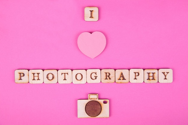 Wooden letters, inscription on a bright pink background.