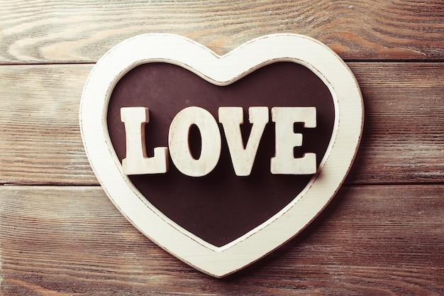Любовь деревянные буквы на доске в форме сердца