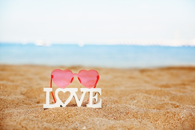 Wooden letters love and pink heart-shaped glasses on a sandy beach overlooking the blue sea
