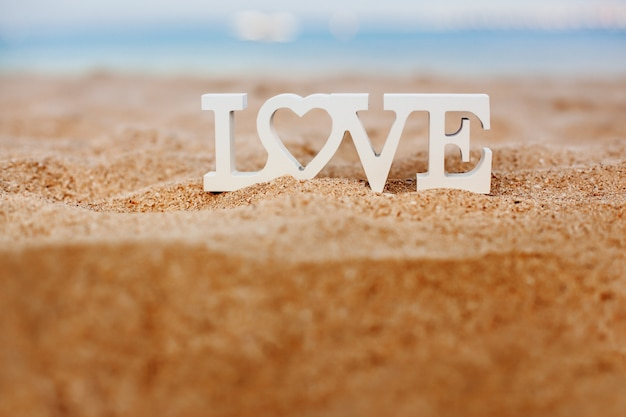 Wooden letters love on a sandy beach overlooking the blue sea