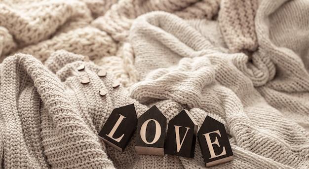Деревянные буквы составляют слово «любовь» на фоне уютных вязаных вещей.