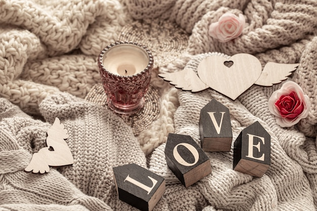 木製の文字は、居心地の良いニットアイテムに対する愛という言葉を構成しています。バレンタインデーの休日のコンセプト。
