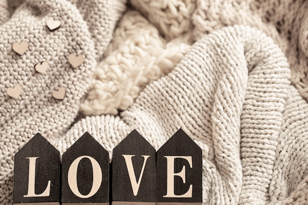 Wooden letters make up the word love on a background of cozy knitted items.
