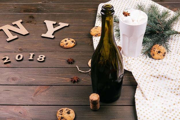 Деревянные буквы «ny 2018» лежат на полу, окруженные печеньем, еловыми ветками, горячим шоколадом, пустой бутылкой вина
