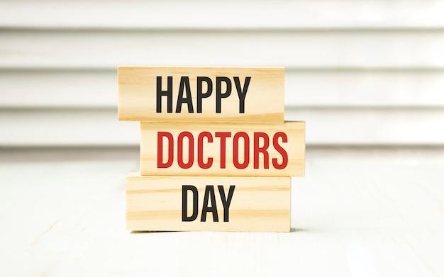 흰색 테이블에 누워 의사의 날 단어의 형태로 알파벳의 나무 글자
