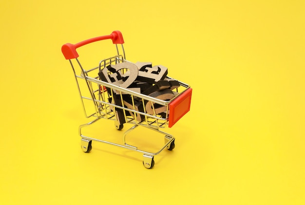 Деревянные буквы английского алфавита лежат в миниатюрной тележке для покупок на желтом фоне cl ...