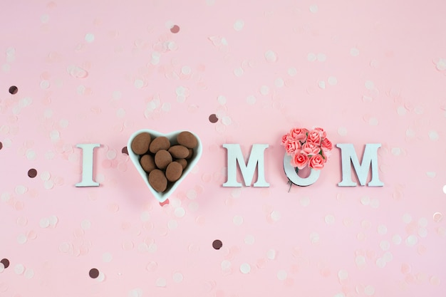 Wooden letters in the phrase i love mom with flowers and chocolate candy on a pink desk.