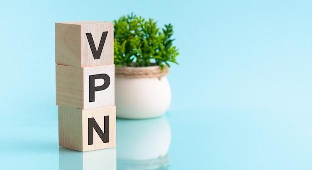 Написание деревянных букв vpn - виртуальная частная сеть. синий фон и цветок на заднем плане.