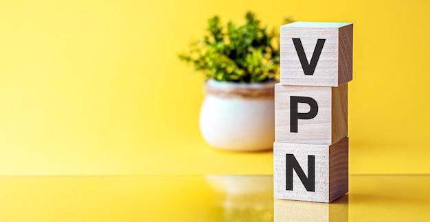 Написание деревянных букв vpn - виртуальная частная сеть. желтый фон и цветок на заднем плане.