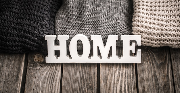 Lettere di legno con la scritta home e maglioni lavorati a maglia