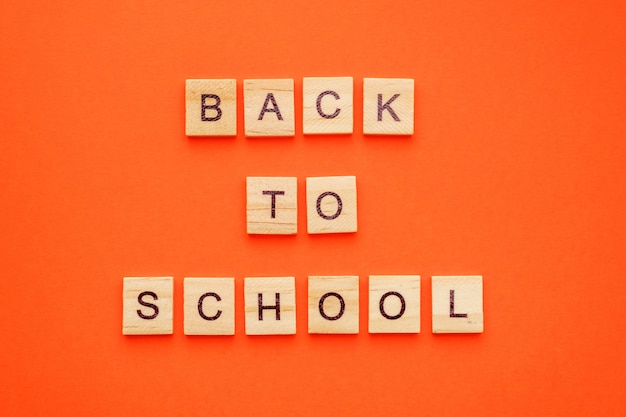 Wooden letters with phrase back to school on orange