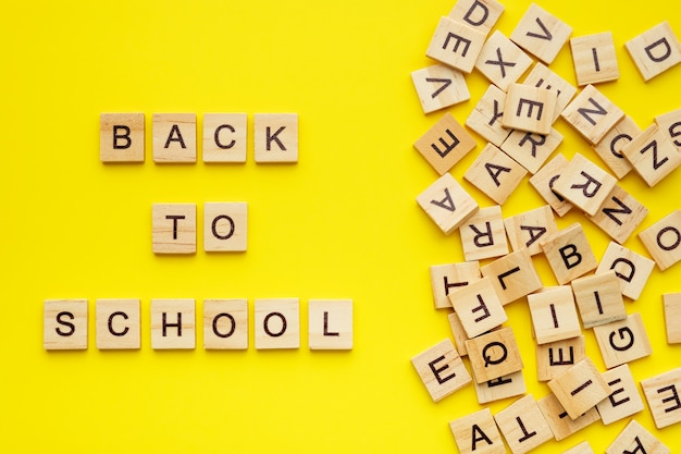 Wooden letters with phrase back to school on yellow background.