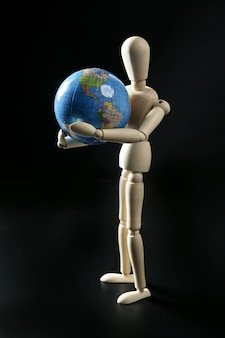 Wooden little mannequin holding the world map