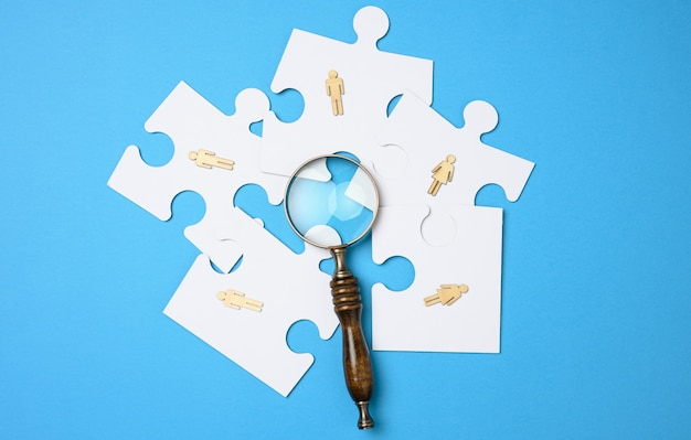 Wooden little men lie on white puzzles around a magnifying glass on a blue background. concept of searching for talented people, recruiting personnel, identifying those capable of career advancement