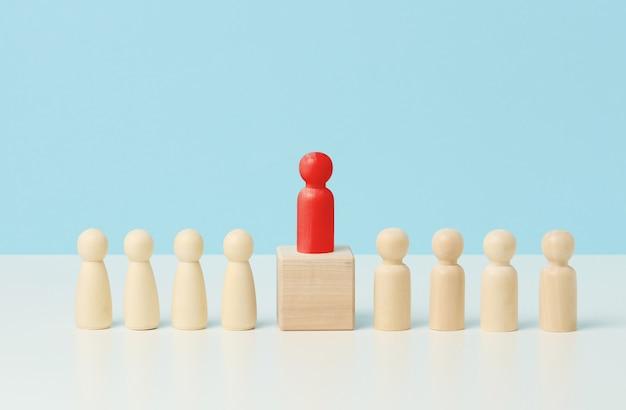 Деревянные человечки на белом столе, красные стоит на деревянном кубе. поиск талантливых сотрудников, сплочение, манипулирование массами, подбор сотрудников в команду