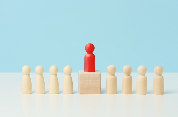 Wooden little men on a white table, red stands on a wooden cube. search for talented employees, rally, manipulation of the masses, selection of employees for the team