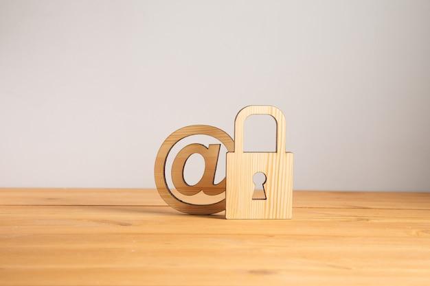 木製の背景にメールサインと木製のロック
