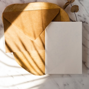 Wooden log and leaf branch with a brown envelope and a white blank on a marble background with leaf shadows