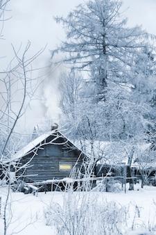 Wooden log old bath beside winter snowy forest