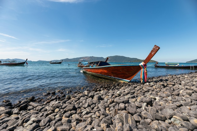 Wooden long tail boat anchored on koh hin-ngam coastline