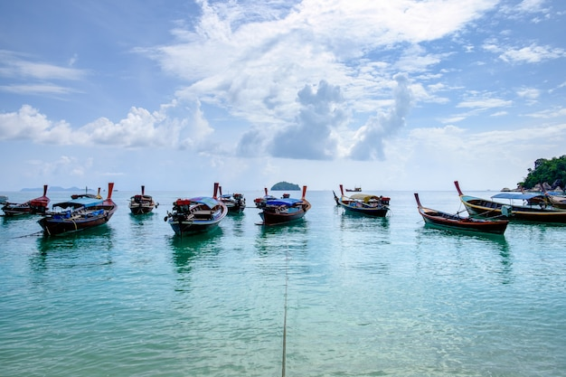 Wooden long tail boat anchored on turquoise seashore with cloudy blue sky