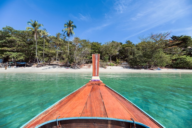 Wooden long tail boat sailing on tropical sea with blue sky