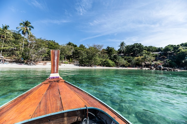 Wooden long-tail boat sailing on turquoise tropical sea at lipe island