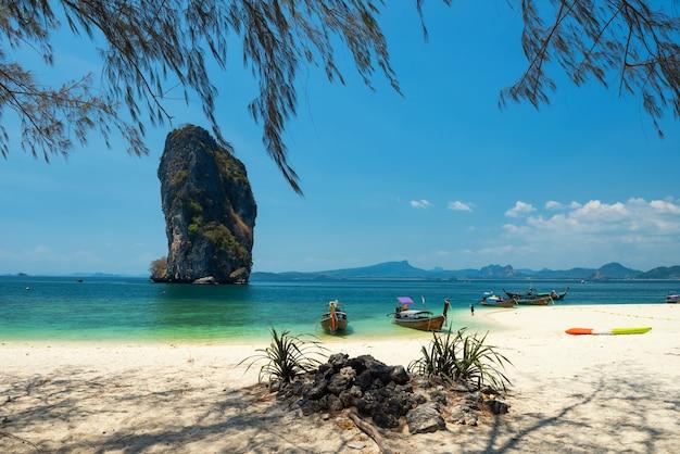 ポダ島のターコイズ ブルーのアンダマン海にある木製のロング テール ボートで、白い砂浜、青い空、タイのクラビの夏にポダ ノック島が描かれています。