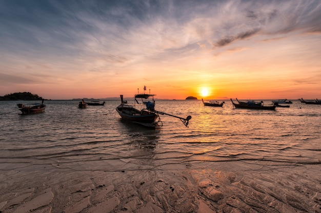 Wooden long-tail boats on tropical sea at sunrise morning beach