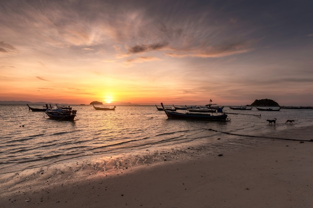 Wooden long-tail boats on tropical sea at sunrise morning